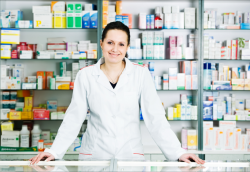 happy and cheerful pharmacist woman standing in pharmacy drugstore